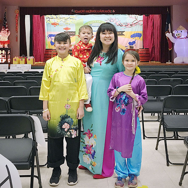 More recent photo of a young mom and her three children, all dressed in colorful Vietnamese clothing.