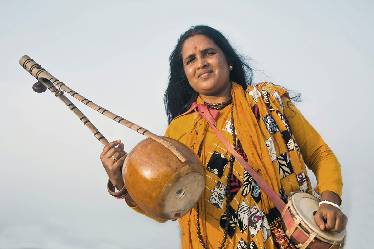 A woman in a yellow tunic holds up a wooden stringed instrument in one hand and a small drum in the other.