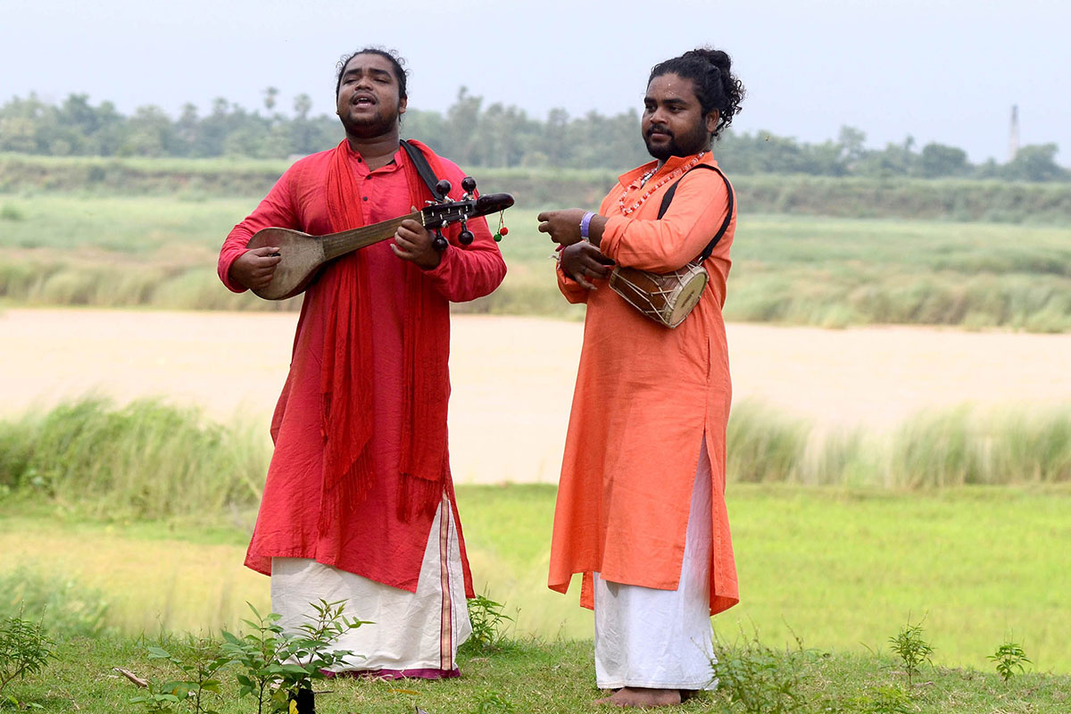 Two men, who appear to be twin brothers, play music with a vast green meadow behind them. The one of the left is in a red tunic, playing a wooden stringed instrument. The one of the right is wearing a bright orange tunic, playing a wooden drum tucked under his left arm.