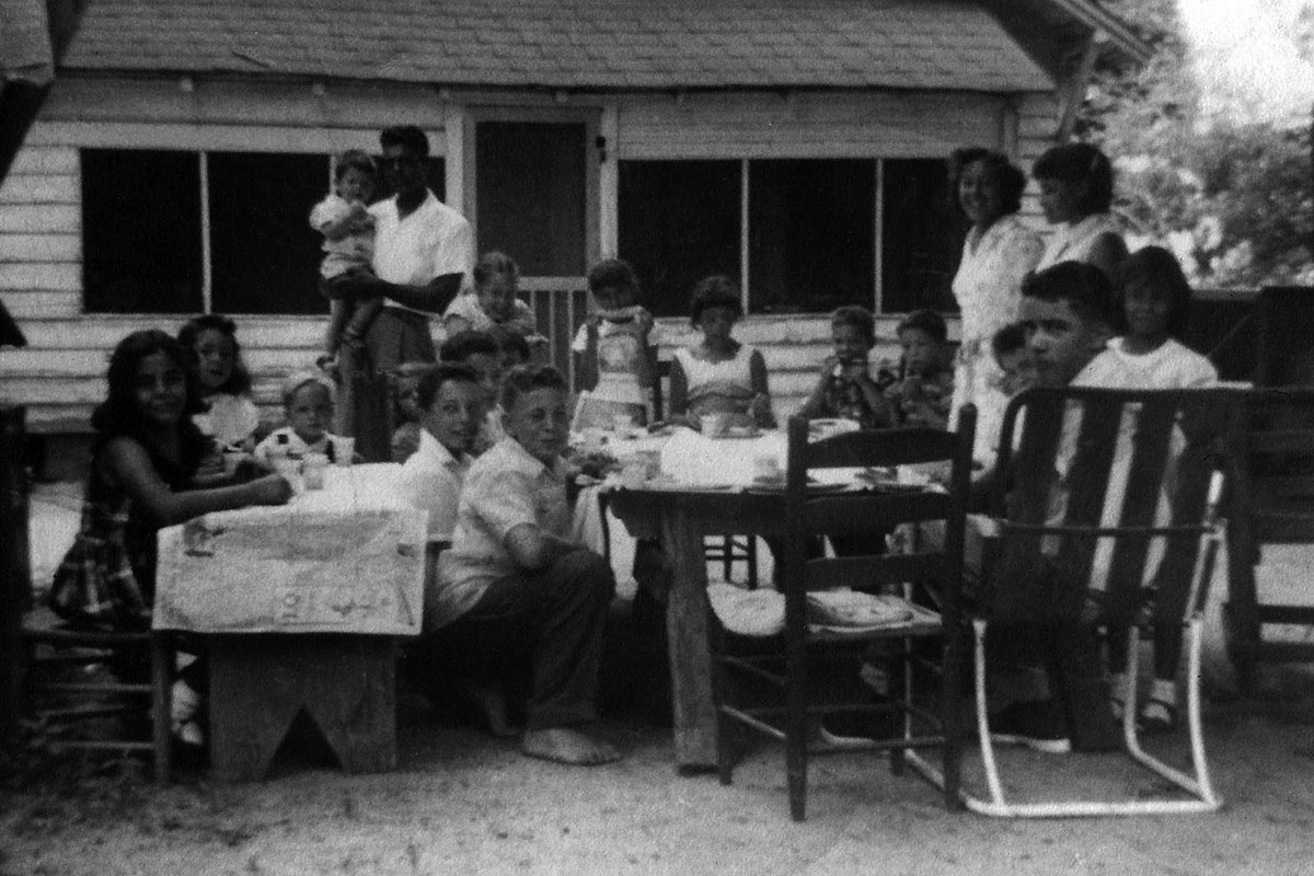 A group of people at tables in a backyard. Black-and-white photograph.