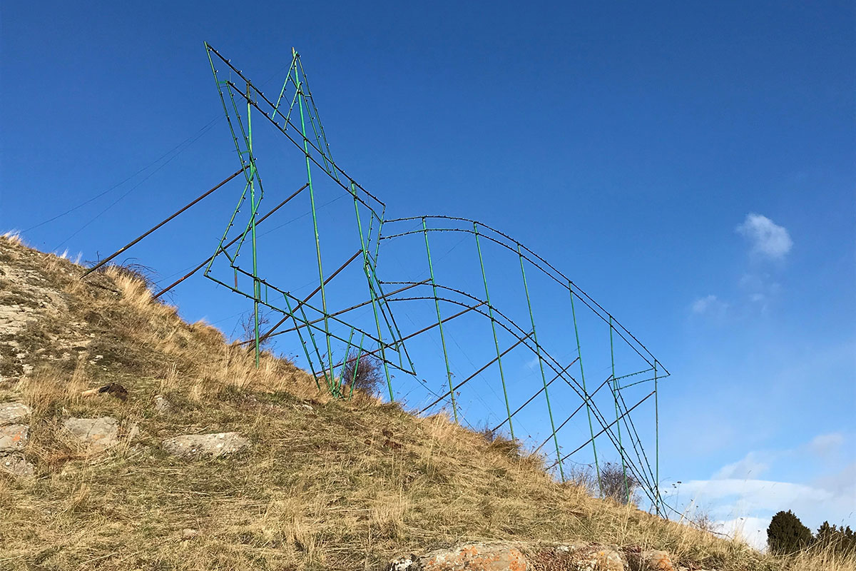 Metal scaffolding in the shape of a giant shooting star standing at the top of a hill.