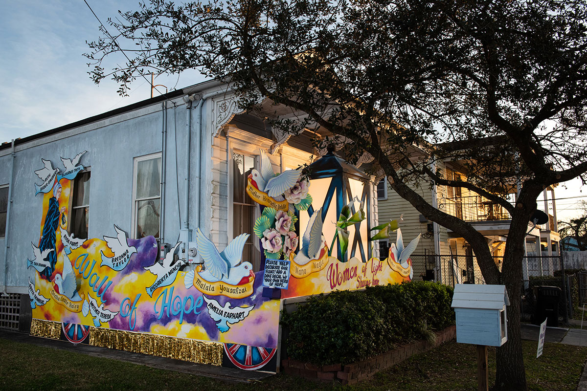 Exterior of a house at dusk, decorated with two-dimensional white doves. Murals read Women Of Light and Wall of Hope, with name of women from history: Mother Teresa, Breonna Taylor, Amelia Earhart, Rosa Parks, and others out of focus.