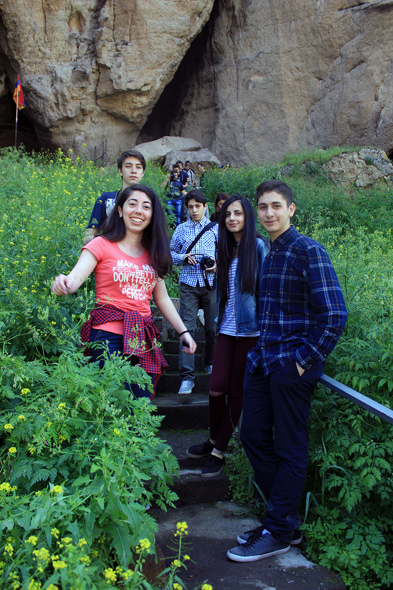 Teens pose on a stairway lined by green shrubs.