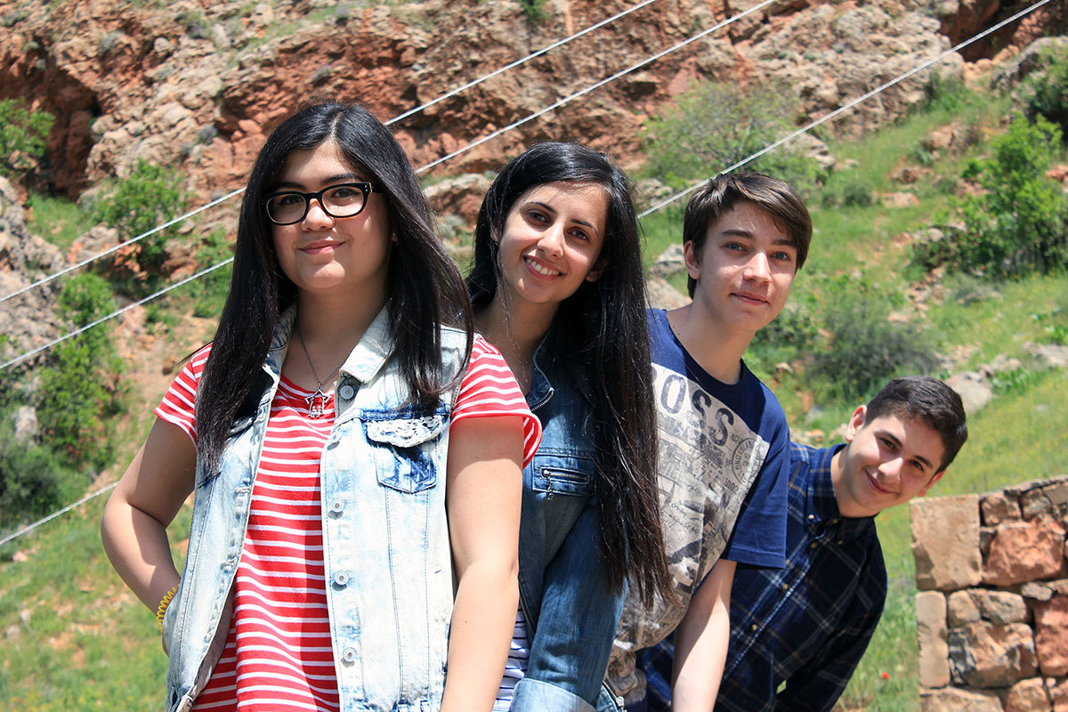 Four teens posing outdoors, fanned out. Alen, in the back, is leaning far to the side.