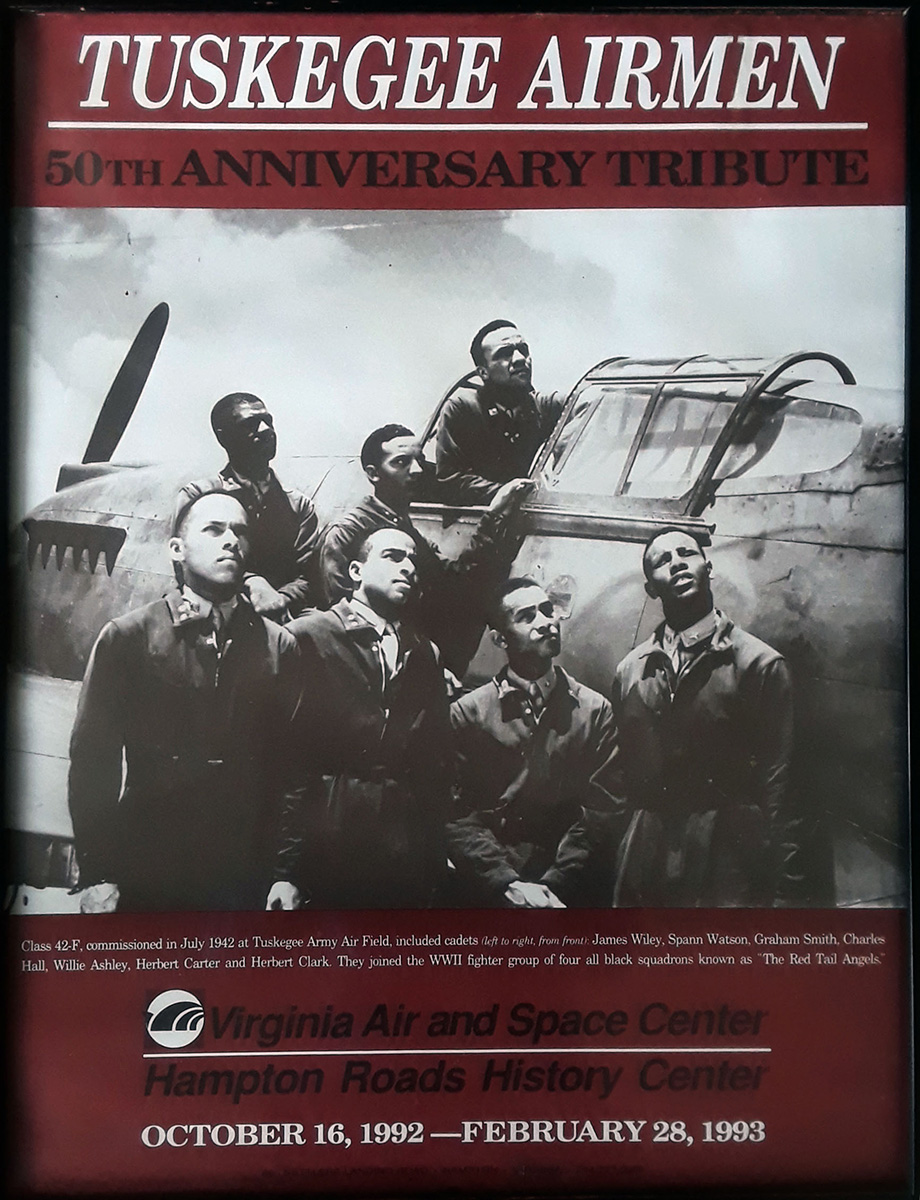 Promotional poster reads: Tuskegee Airmen 50th Anniversary Tribute / Virginia Air and Space Center / Hampton Roads History Center / October 16, 1992 - February 28, 1993. Photo shows seven black pilots posing in and around a plane.