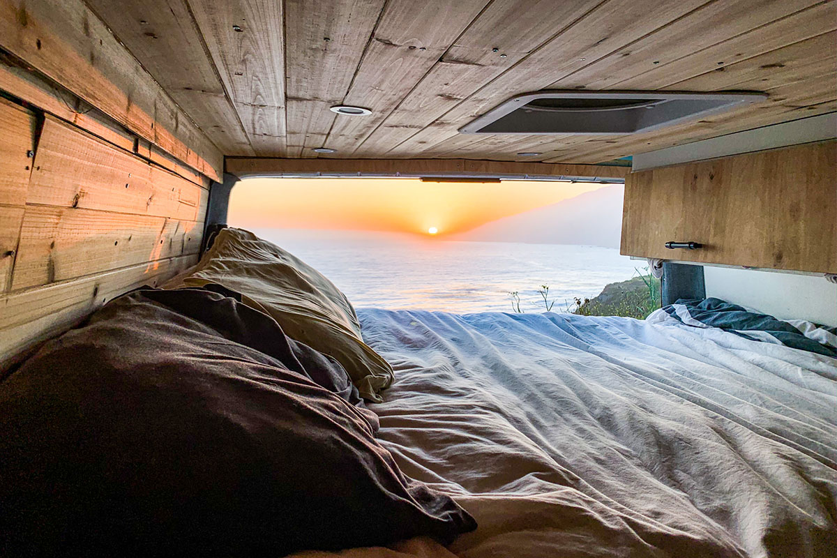 From inside a van, a bed and wood panelling in the foreground, and a flowing sunset over the ocean through the open back door.