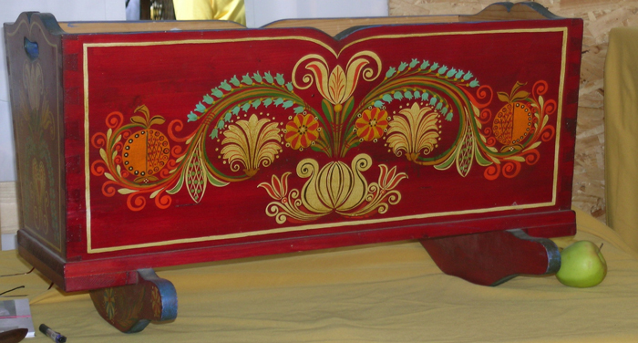 At his crafter's booth, Sütő displays this traditional red cradle among other hand carved and painted pieces.