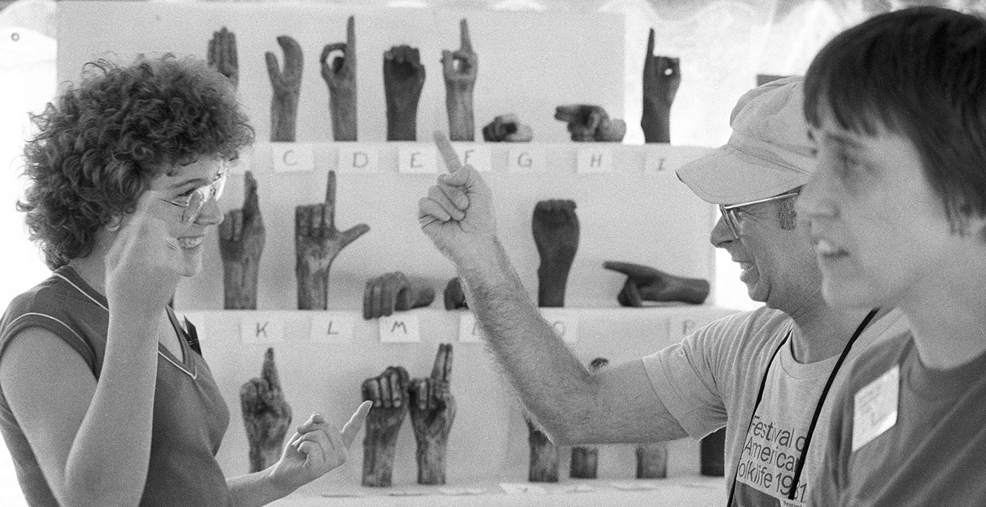 A man and a woman communicate using ASL, with a third person in the foreground looking on. Behind them is a display of sculptures of hands, depicting the ASL alphabet. Black-and-white photo.