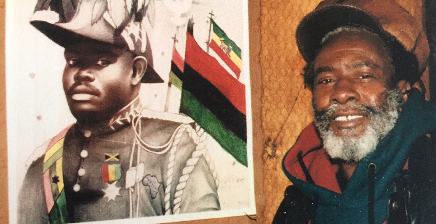 A Black man smiles, posing next to a poster of a Black man in military dress and the Pan-African flag.