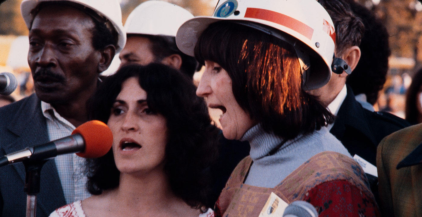 A group of people, with two women in the forefront, sing together outdoors. Some of them, including one of the women, are wearing hard hats.