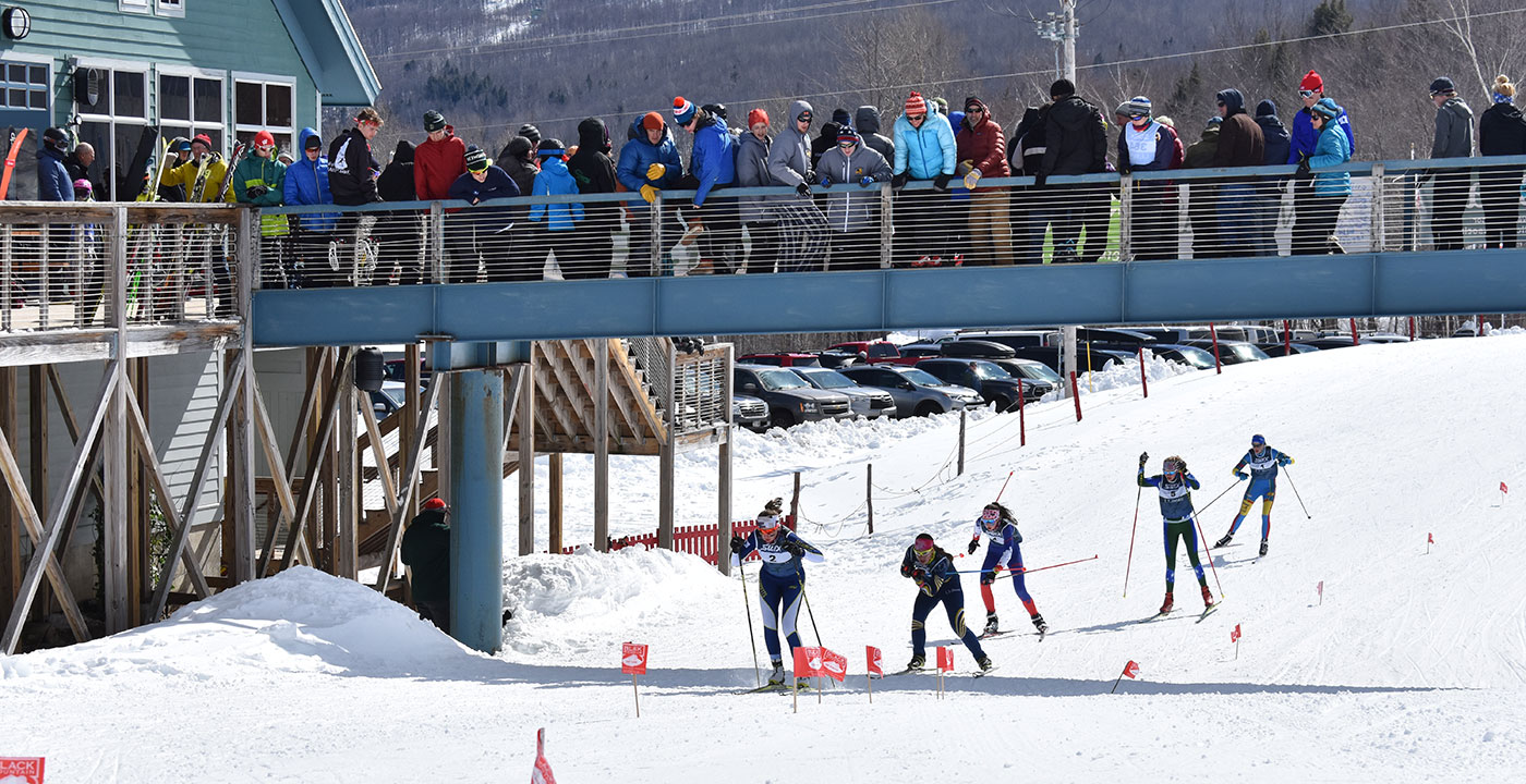 Five cross-country skiers on a race track, with a crowd of people on a bridge overhead.
