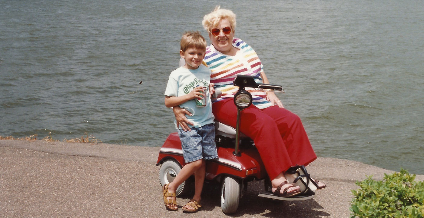 Old color photo of a young boy standing next to an older woman on an electric mobility scooter in front of a lake.