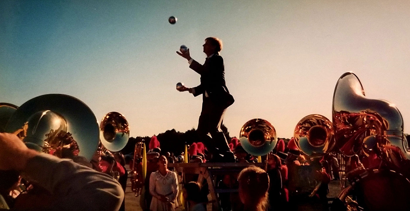 At dusk, silhouetted figure of a man juggling, surrounded by the glinting bells of sousaphones and marching band members in uniform.