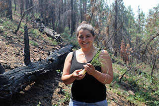 A young women holds a tuft of long grass, smiling on a forested hillside that looks like it's recovering from a fire.