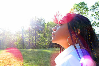 A Black Latinx woman with long braids and gold hood earrings standing in a park, with red and purple spots of lens flares.