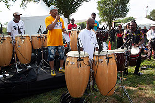 Man addresses an outdoor crowd on microphone as other men on congas around him prepare to perform.