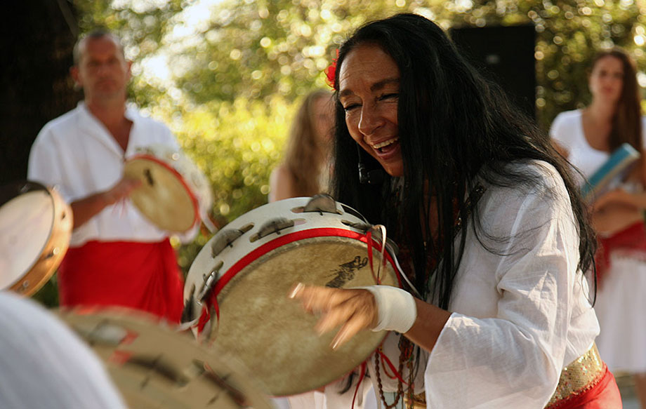 A woman in flowy white blouse and red sash plays a wooden frame drum with her hands, demonstrating for others in the same outfit around her.