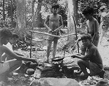 Black-and-white photo of a group of young boys preparing a meal over a fire pit at Camp Boiberik in the summer of 1936