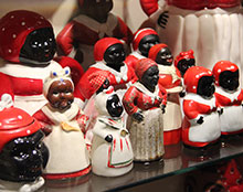 Several ceramic mammy dolls, all in red blouses and  headscarves and white aprons, lined up on a museum display shelf.