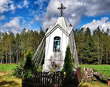 Outdoor shrine, like a miniature church, surrounded by ribbons, picket fence, and shrubs.