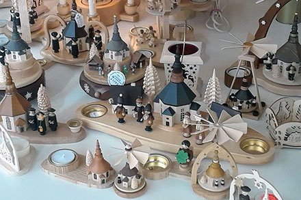 A display of wooden toys that seem to form a village: steepled churches, evergreen trees, windmills, figures of people in uniform, all in natural blonde wood and earthen tones.