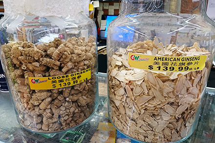 Two glass jars of dried ginseng roots are sold in different shapes in the Asian grocery store, priced at $139.99/lb