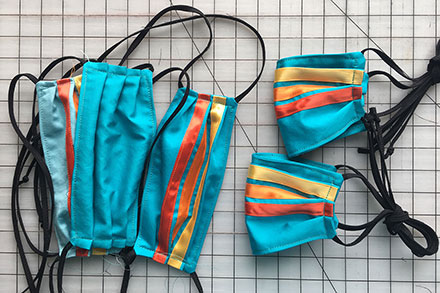 A stack of face masks on a gridded work station. They are turquoise with black straps and shiny ribbons sewn from side to side in stripes: red, orange, yellow.