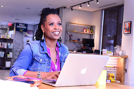 A Black woman sits working on a laptop at a café/deli, smiling into the distance.