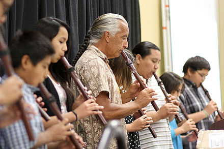 A row of people lines up playing flutes. Most are young students, and in the middle is an older man with a long gray braid.