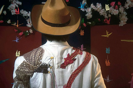 The back of a person wearing a brown fedora and white jacket embroidered with a bald eagle on the left shoulder fighting a red dragon on the right. Origami cranes are hanging in the background.