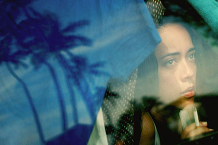 Film still of a young woman inside a vehicle, looking outside and holding a cigarette. We see reflections of palm trees in the window.