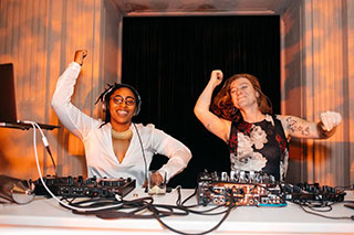 Two women dance in sync at a DJ booth, their arms in the air.