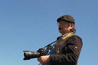 An older Asian man standing against blue sky background, holding a DSLR camera with big lens and a headset.