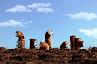 From a distance are pictured an arrangement of nine rusty pipes, bent and opening at various angels are placed in the dark soil. The visible openings are painted to appear like a blue sky with white, fluffy clouds.