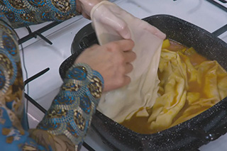 A woman's hands layer a thin sheet of dough into a pot of stew on the stove