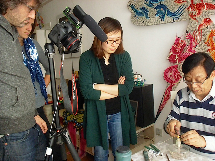 Jing Li (center) interviews master kite maker Ha Yiqi in Beijing, along with photographer Joshua Cogan and Marketplace coordinator Halle Butvin.