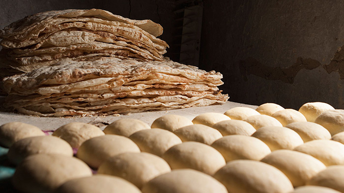 Baked lavash rests next to mounds of dough ready for baking. Photo by Sossi Madzounian, Smithsonian Institution