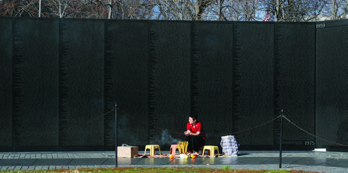 Genevieve Erin O'Brien performs a ritual for Vietnam Suitcase at the Vietnam Veterans Memorial in Washington, D.C.
