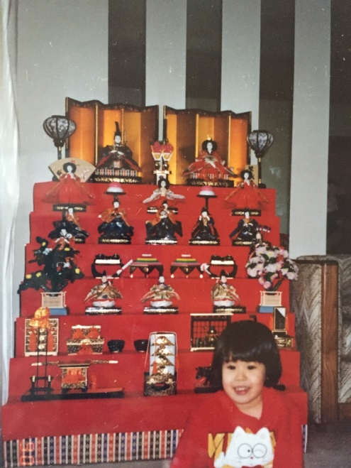 Five-year-old Christine posing in front of her mother's doll display for Hinamatsuri.