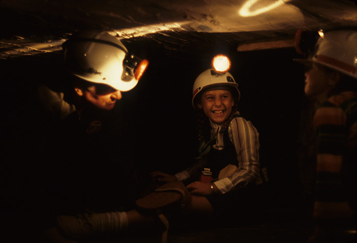 A coal miner from West Virginia shows two young visitors the challenges of working in the confined spaces of a simulated coal mine.