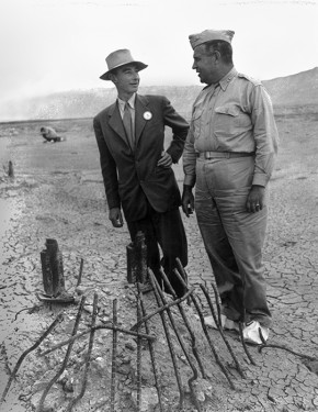 Inspecting the remains of Ground Zero at the Trinity site are J. Robert Oppenheimer, the Manhattan Project's chief scientist (left), and General Leslie Groves, the Project's director.