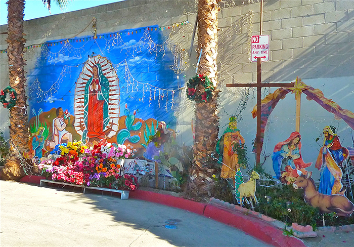 A mural and altar honoring la Virgen de Guadalupe and a nacimiento are installed on a dead-end street wall created by a one of several freeways that cut through the neighborhood of Boyle Heights.