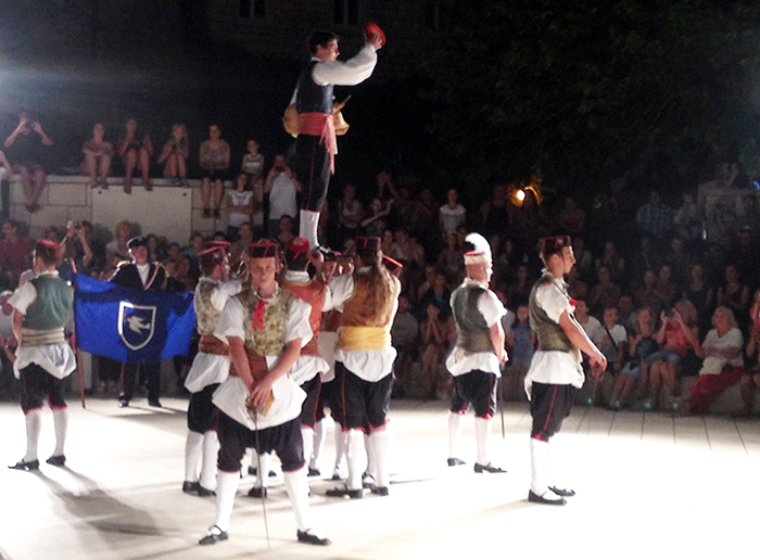 The Vela Luca Kumpanjija group lift their bagpiper on a bed of swords at the 2014 Sword Dance Festival.