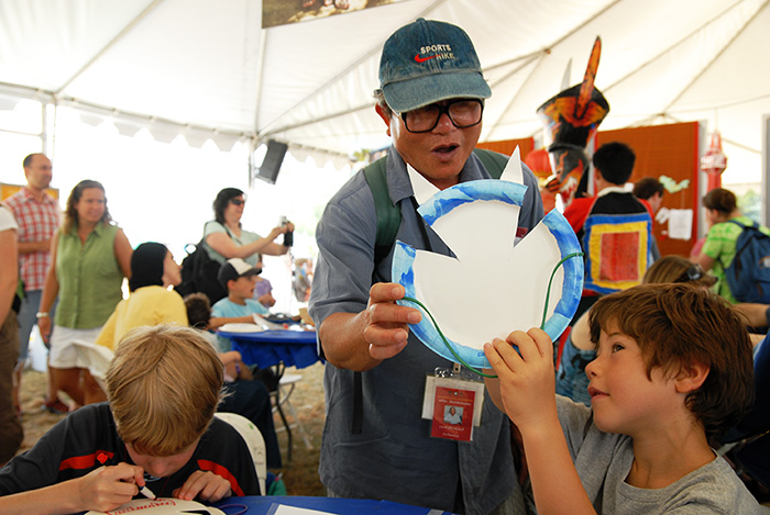 Suriya Smutkupt, Wirayu's translator, examines the work of a mask maker-in-training at the Folklife Festival. Photo by Nancy Libson, Ralph Rinzler Folklife Archives