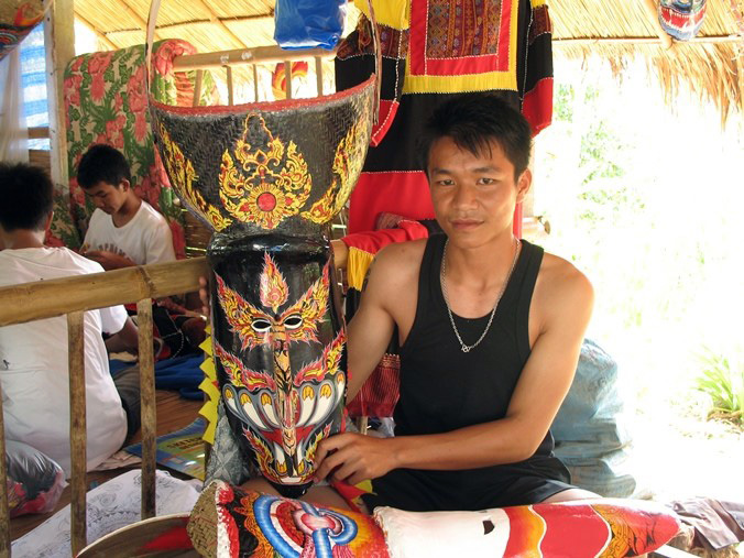 At work in Thailand, Wirayut Natsaengsri shows a Phi Ta Khon mask he made with another one in the works in his lap. Photo by Sunee Prasongbandit, Ralph Rinzler Folklife Archives