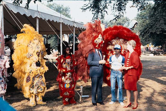 A reporter tries on the elaborate dress of the Mardi Gras Indians during an interview at the 1985 Folklife Festival. Photo by Jeff Tinsley, Ralph Rinzler Folklife Archives
