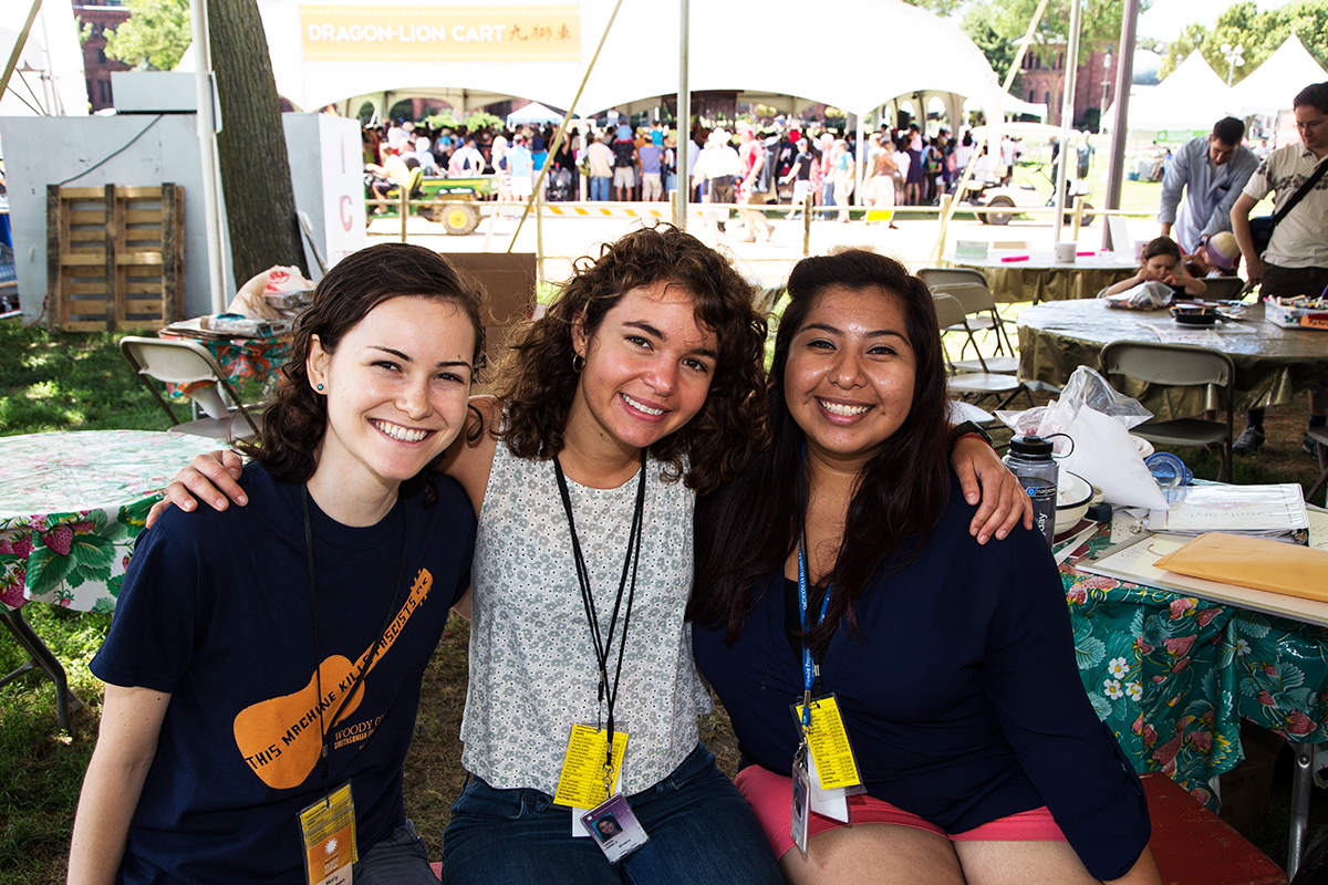 Interns Molly Henderson, Emma Lewis, and Julia Aguilar in the Family Style tent at the 2014 Folklife Festival.