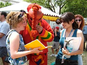 Laura Service (left) and Eleana Diaz interview an atsara masked dancer from Bhutan. Photo courtesy of Sarah Searcy